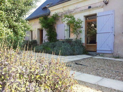 une photo d'un gîte avec un jardin et une petite terrasse
